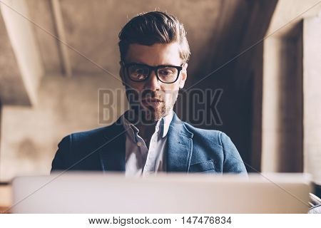 Businessman at work. Low angle view of confident young man in smart casual wear working on laptop while sitting at his working place in office