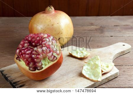 Pomegranate fruit cut dissect on wooden background.