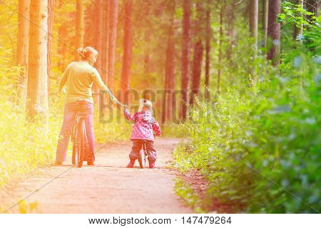 mother and little daughter riding bikes in summer forest
