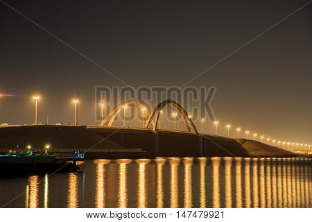 HIDD, BAHRAIN - SEPTEMBER 10, 2016: Night shot of the beautiful bridge connecting Juffair and Hidd areas, a view from Prince Khalifa Bin Salman Park