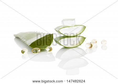 Aloe vera gel caps. Aloe vera sliced leaf and aloe vera gel caps isolated on white background.