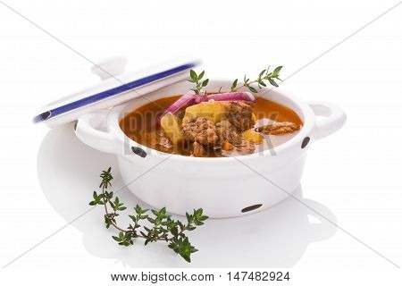 Delicious goulash soup in white pot on white background. Culinary traditional goulash eating.