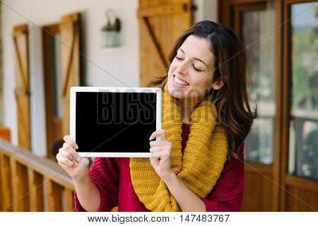 Woman Showing Tablet Screen Outside Home On Autumn