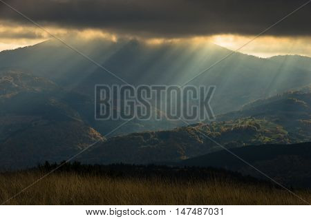Heavy overcast sky with sunrays over meadows and colorful forests at autumn, mountain Goc, Serbia