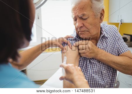 Female doctor giving an injection to a patient at the hospital