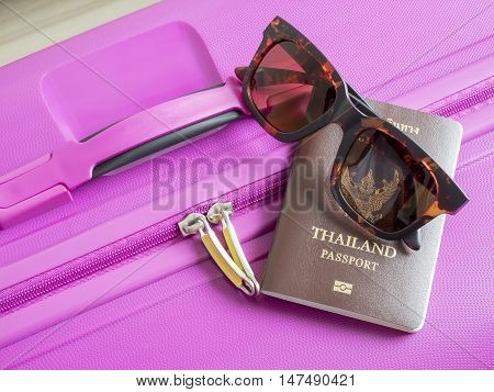 Closeup Thailand passport and sunglasses on pink suitcase