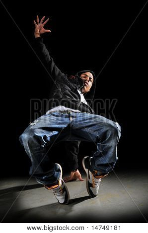 Hip hop man dancing over a dark background poster