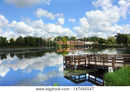 Fishing dock and blue sky is reflected in this landscape image of Stoughton Wisconsin and the Yahara River.