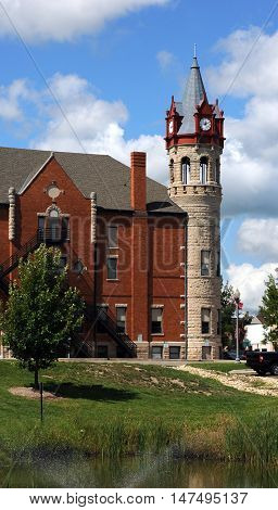 Side view of the Stoughton Wisconsin Opera House and City Hall. Round tower houses four clocks in dormers with Victorian architecture.