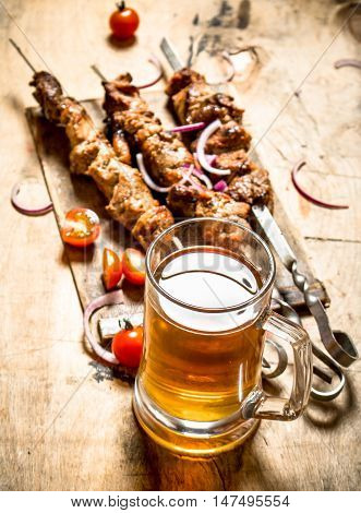 Beer with pork Shish kebab and tomatoes. On a wooden table.