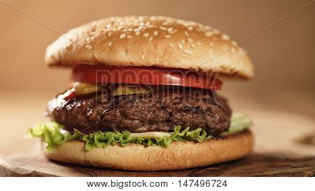 fresh homemade burger with marble beef, cheese and vegetables on olive board, shallow focus