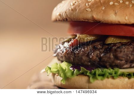 closeup fresh homemade burger with marble beef, cheese and vegetables on olive board, shallow focus
