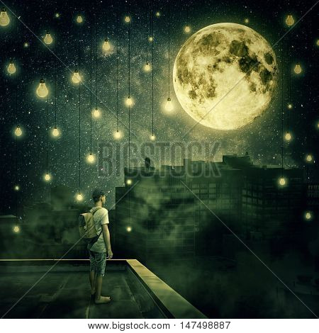 Young boy stay on the rooftop looking at the full moon. Mysterious night with suspended lightbulbs as stars over the foggy city