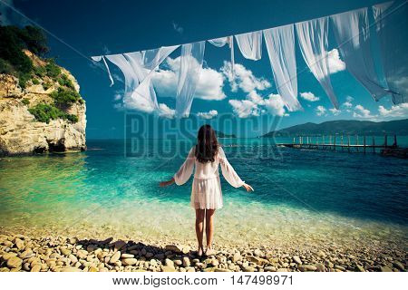 Young brunette woman in summer white dress standing on beach and looking to the sea. Caucasian girl relaxing and enjoying peace on vacation. Greece Island.