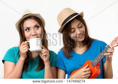 Woman relaxing.They are plays ukulele and drinking.
