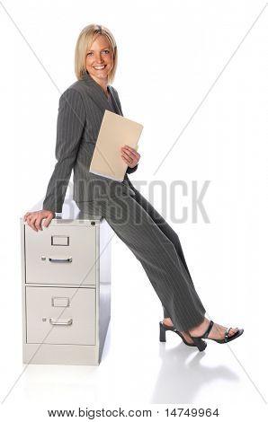 Businessman holding folder sitting on file cabinet