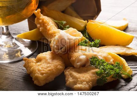 Traditional British fish and chips close up on the black background with glass of beer
