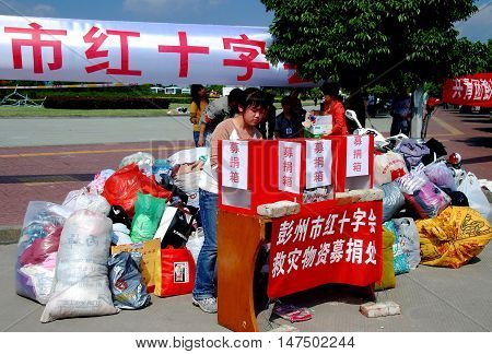 Pengzhou China - May 15 2008: Volunteer at a donation center accepts clothing and cash for the victims of the 12 May 2008 earthquake disaster