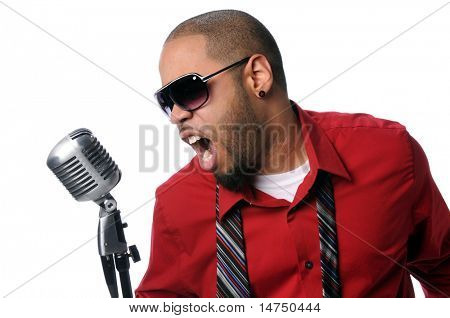 Young African American man singing into vintage microphone isolated over white