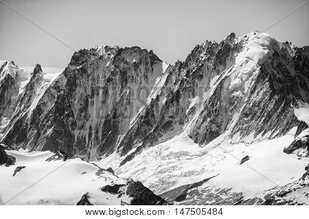 A black and white detailed shot of Aiguille Vert in the Chamonix valley seen from the summit of Haute Cime in the Swiss alps.