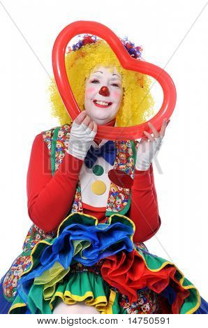 Adult female clown holding red heart balloon