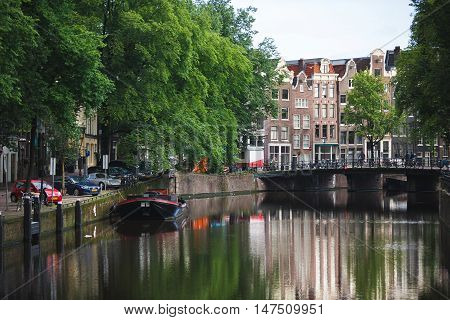 Amsterdam Netherlands - July 03 2016: The traditional Dutch houses reflected in water on Singel street sunny morning