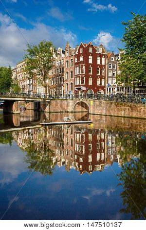 The traditional Dutch houses reflected in water on Singel street Amsterdam