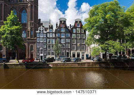 Amsterdam Netherlands - July 02 2016: The traditional Dutch houses nearby the De Krijtberg Church located on Singel street sunny day