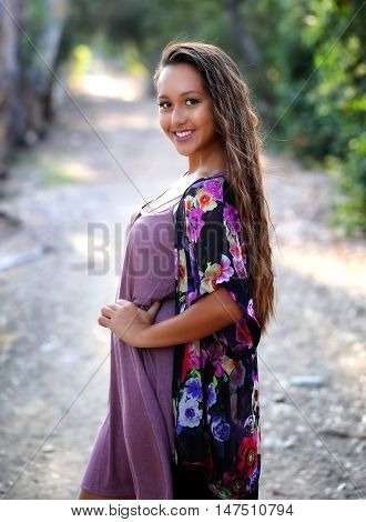 Beautiful young girl in a purple dress and floral kimono on a dirt path