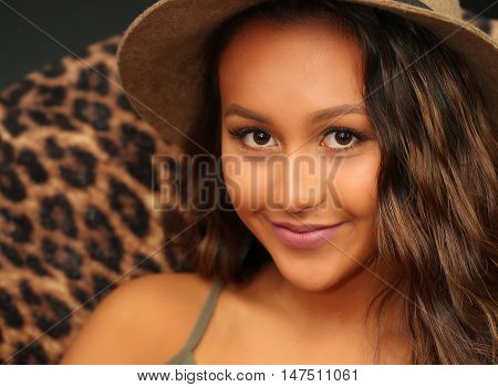 Pretty girl with long, wavy hair, sitting in a chair, relaxing and happy