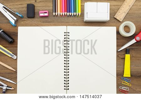 Business concept:stapler,glue,scissor,cutter,tape,pen,pencil,clip,ruler,rubber,diary ,divider,sharpener,wooden block calendar and color pencil on wooden