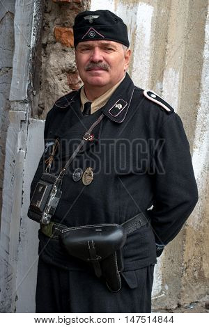 Gatchina, Russia - September 11, 2016: The historical reconstruction of World War II. A man dressed in a form of the Nazi officer. He holster with a pistol and a retro camera.