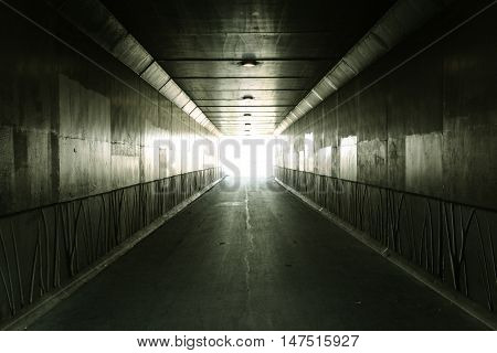 Light At The End Of The Tunnel.  Light illuminates the end of an urban concrete tunnel. In panoramic orientation with copy space.