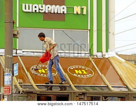 MOSCOW, RUSSIA - August 14, 2016: Young adult man standing on the roof washes mop the roof of the fast food. August 14, 2016 in Moscow, Russia