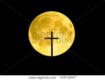 A big yellow full moon with a church's cross infront it.