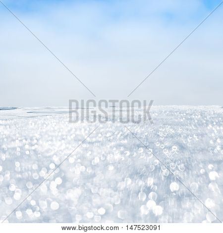 A soft focus image of sea foam from Pacific ocean waves and surf. The image foreground is defocused in order to create bokah light effects.