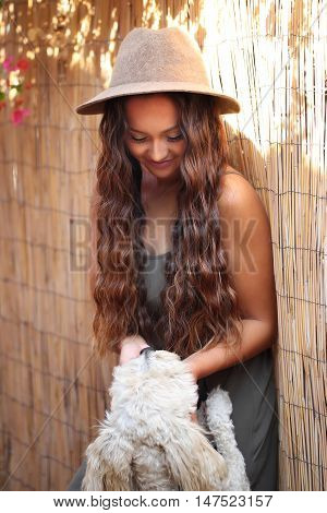 Pretty young girl with long hair petting a dog