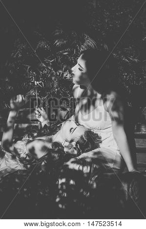 Two sisters. Girl lies on the lap of an older sister. Family time. Human relationships. Black and white photography.