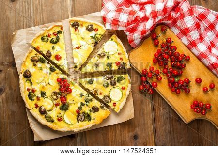 Freshly baked homemade pie quiche lorraine on a wooden table