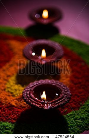 beautiful diwali diya or oil lamp over colourful rice grain rangoli, selective focus