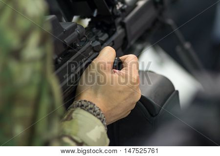 Soldier holding a gun machine at the ready. Weapon