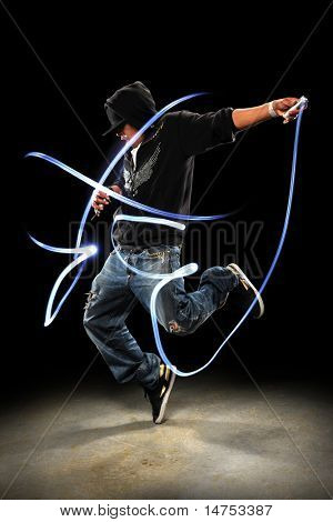 Hip hop dancer performing with LED lights dancing over dark background with spotlight poster