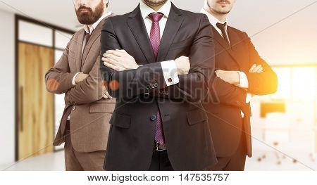 Three businessmen in suits standing in empty office with computers. Concept of successful business people. Toned image.