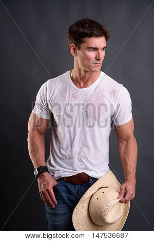 The sexy cowboy is holding a hat.