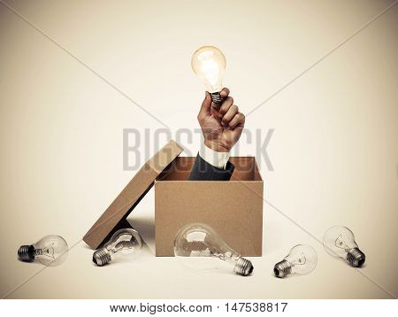 Hand of a businessman holding a turned on light bulb coming out from a brown paper box surrounded by old incandescent light bulbs / Business with new idea and innovation concept
