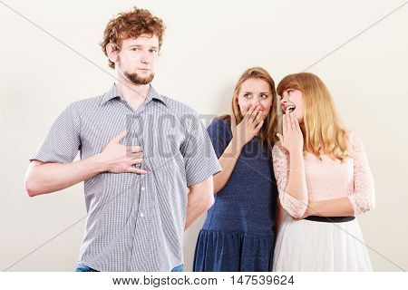 Young women friends talking gossiping about man. Two women whispering sharing secret news.