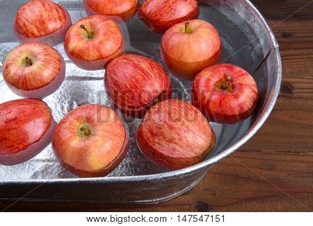 A metal tub filled with water and apples for the Halloween custom of Apple Bobbing.