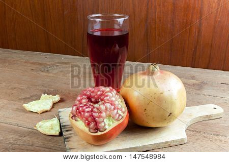 Pomegranate fruit cut dissect and pomegranate juice on wooden background.