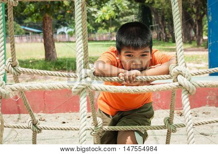 cute asian boy sitting alone at playground