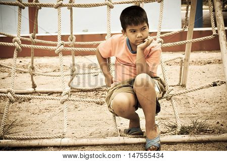 asian boy sitting alone at playground vintage tone